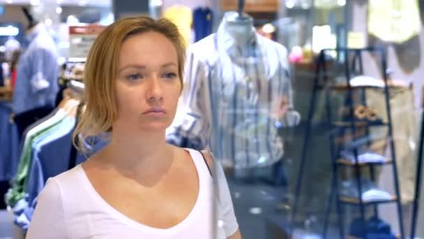 nákupní koncept, Žena na panáky za skleněné vitríny v nákupním centru při pohledu na oblečení