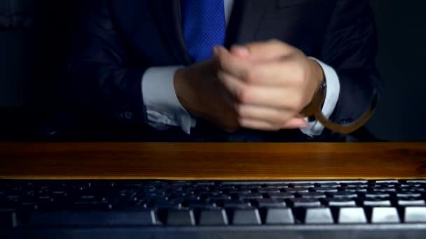 Close-up, mani di un uomo daffari lavorando su una tastiera di calcolatore in manette. concetto di criminalità informatica, workaholism