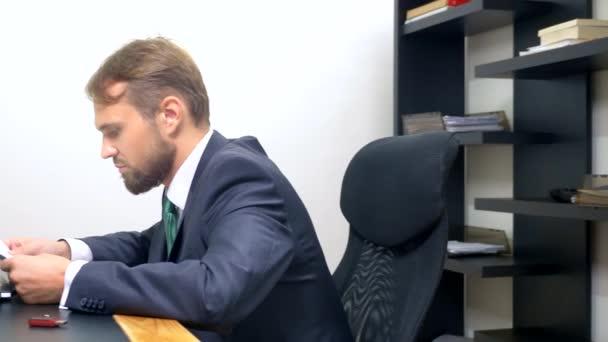 Irodai flörtölni. Vonzó nő piros overall egy mély nyakkivágással flörtöl az asztalnál kollégájával. ember nézi a mellkasát egy nő az irodában