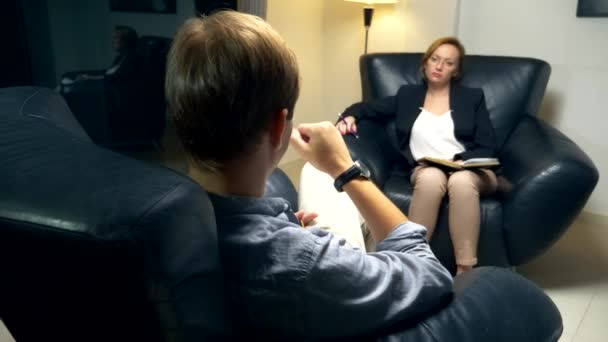concept of negotiation, psychological counseling. A woman with a notebook communicates with a successful man. sitting in the evening in the office in a leather chair.