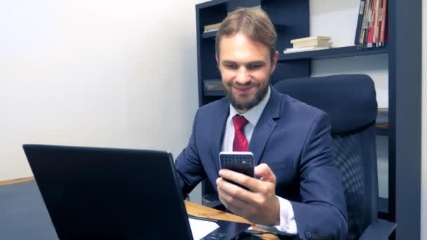 Close-up. Podnikatel používající mobilní telefon a s úsměvem, při práci na přenosném počítači v kanceláři.