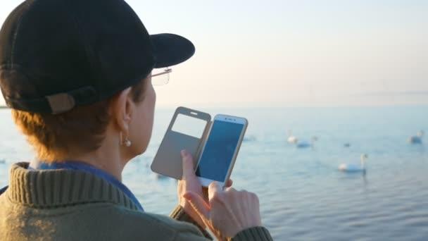 Eine ältere Frau, die am Strand spaziert, macht ein Foto von weißen Schwänen, die im Meer schwimmen, auf ihrem Smartphone