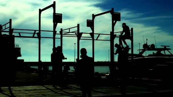silhouettes of people against the blue sky training on the horizontal bars on the beach at the pier with yachts
