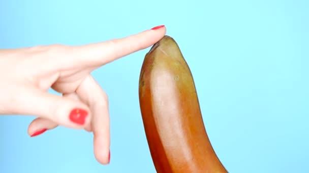 Női kezek piros manikűr érintéssel kék alapon piros banán