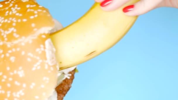 Gesundes Ernährungs- und Ernährungskonzept. Banane und Hamburger stehen. Spaß Fast-Food-Projekt