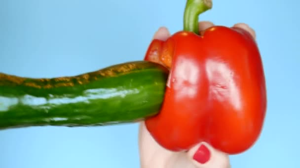 Früchte auf blauem Hintergrund. Konfrontation von frischem Gemüse von Gurken und rotem Paprika, Spaß Fast-Food-Projekt