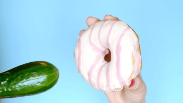 Das Konzept einer gesunden Ernährung und Ernährung. Eine Gurke und ein weiß-rosa Donut. Spaß Fast-Food-Projekt