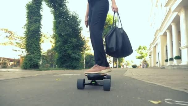 Eine moderne Geschäftsfrau in schwarzem Anzug, rosa Turnschuhen, Sonnenbrille und schwarzer Tasche reitet auf einer Straße in der Stadt. das Konzept der seltsamen Abenteuer der Menschen