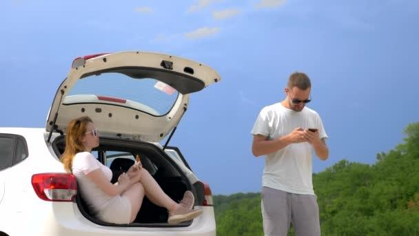 Výlet autem a dva milenci muži a ženy mají svačinu, když sedí v kufru auta proti modrému nebi a horám