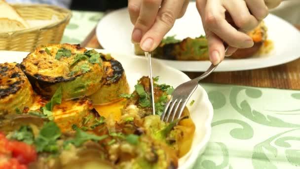 Grilovaná zelenina v restauraci. Žena sní s nožem a vidličkou grilovanou zeleninu a smažený kebab