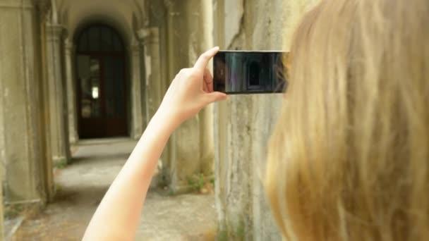 junge Frau fotografiert mit dem Handy eine Kolonnade eines alten Schlosses