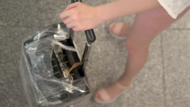 concept of tourism and travel. close-up. Female hands hold the suitcase handle while standing in line at the airport