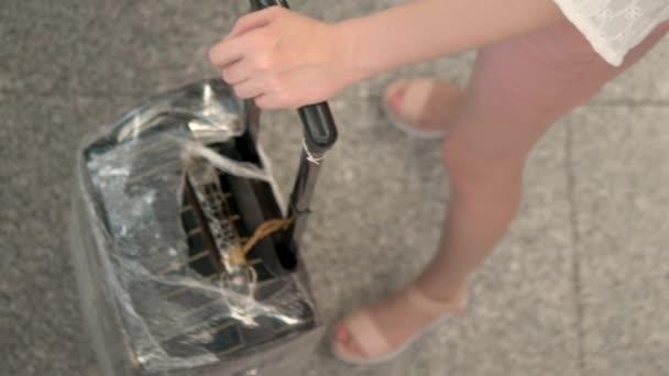 az idegenforgalom és az utazás fogalma. Közeli. Női kéz tartsa a bőrönde fogantyú állva sorban a repülőtéren