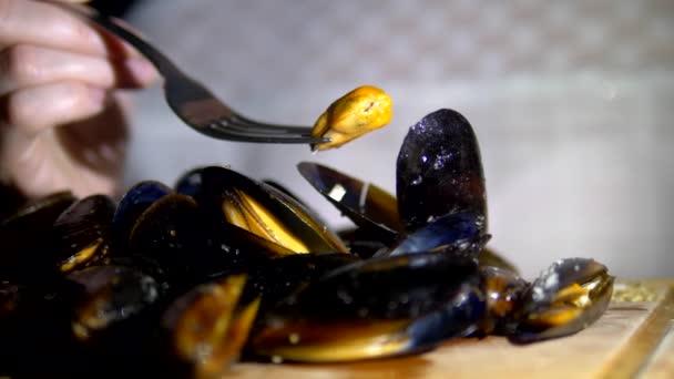 Meeresfrüchte, Restaurant Meeresfrüchte. Weibliche Hände in Großaufnahme. Frau isst Miesmuscheln mit Gabel im Resotran