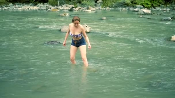 summer holiday concept. a woman in a bathing suit and shorts goes over a mountain river to a ford