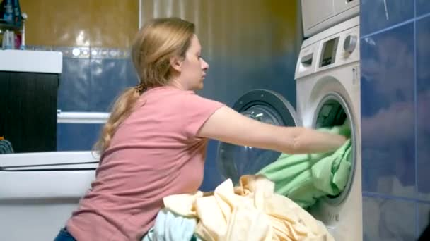 concept of washing at home. woman puts laundry in the washing machine