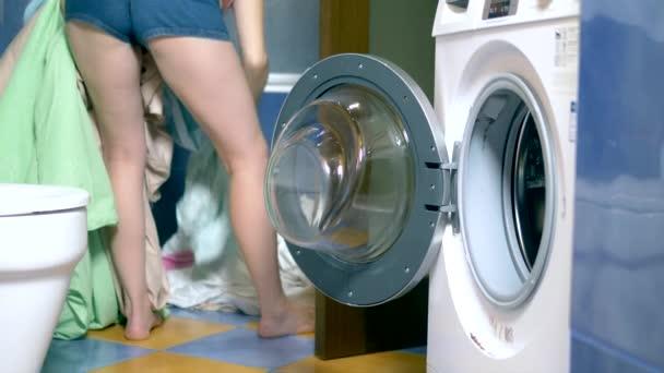 Konzept des Waschens zu Hause. Frau legt Wäsche in die Waschmaschine