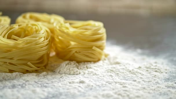 Fettuccine, raw pasta, closeup lie in white flour on a wooden table