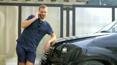 car accident concept. man in a state of shock talking on the phone after a car accident, standing by a car with a broken bumper