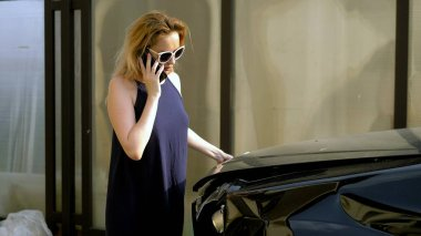 car accident concept. woman in a state of shock talking on the phone after a car accident, standing by a car with a broken bumper