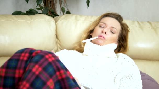 junge kranke Frau im Pullover unter einem Karo mit Fieber überprüft ihre Temperatur mit einem Thermometer zu Hause