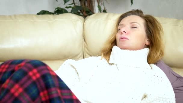 Kaukasische Frau, mit Papierserviette niesen, in einem Pullover unter einer Decke auf der Couch, erleben AllergieSymptome, erwischt eine Erkältung.