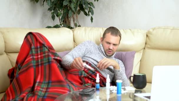Ein junger Kranker im Pullover unter einem Karo mit Fieber überprüft zu Hause mit einem Thermometer seine Temperatur