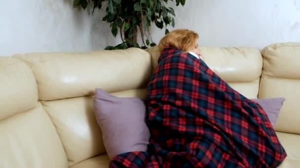 Frau in einem Haus auf dem Sofa liegt unter einem karierten zu Hause leiden an Kälte und Fieber. Das Konzept des Erkältungs- und Grippevirus