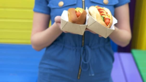 děvče má v ruce dva lahodné hot dogy na ulici za letního dne
