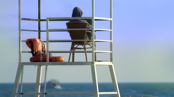 Ein unkenntlich gemachter männlicher Bademeister in einem Rettungsturm am Strand. Sicherheitskonzept für den Seeverkehr