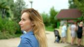Egy szép fiatal szőke nő sétál a város körül, és körülnéz érdeklődésével, a kamera követi őt a háttérben egy mozgó tömeg az emberek, elmosódott