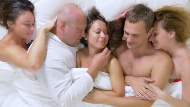 Konzept-Sex-Clubs, Swing-Clubs, Lifestyle-Clubs, formelle, informelle Gruppen. Gruppe von Liebenden Mann und Frau auf einem Bett King Size unter einer weißen Decke liegend