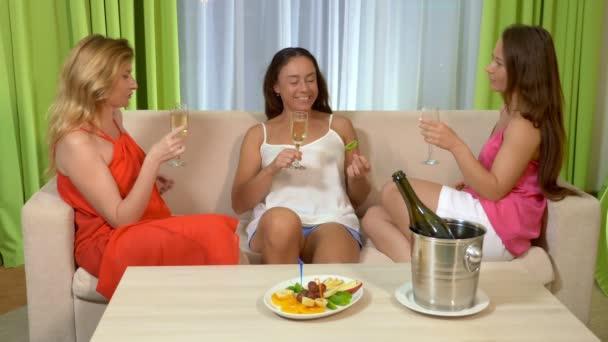 Tři krásné ženské přítelkyně popíjí šampaňské a baví se bavit na večírku doma.