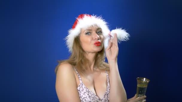 pin-up lány retro smink egy szilveszteri kalap tart egy pohár pezsgőt. Kellemes karácsonyi ünnepeket és boldog új évet. kék háttér, másolási tér