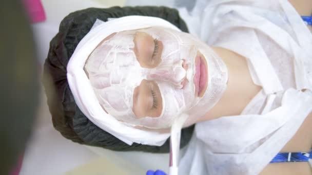 Fogalma kozmetológia. Közeli fel egy kozmetikus alkalmazása egy fehér maszk ecsettel egy Womans arc.