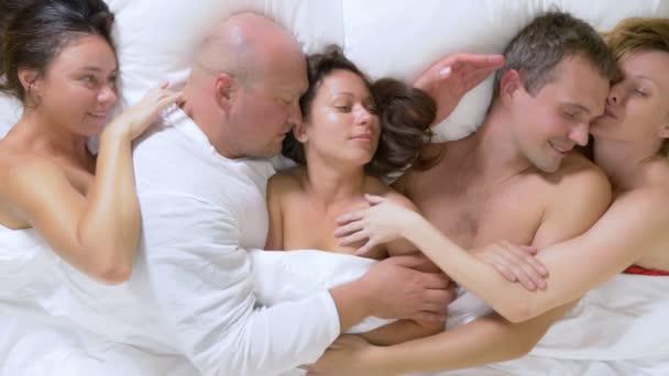 Konzept Sexclubs, Swing Clubs, Lifestyle Clubs, formelle, informelle Gruppen. Gruppe von Liebhaber nera mann und frauen liegen auf einem Bett Kingsize unter einer weißen Decke