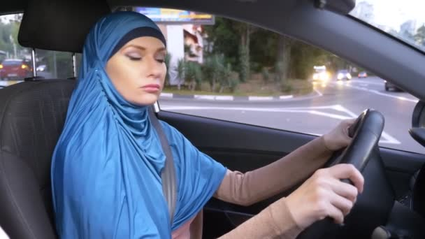 beautiful muslim woman in blue hijab driving a car. rides during the day on the streets of the city.