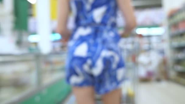 Lidé v supermarketu, rozmazané pozadí. Kupující výběr produktů v supermarketu.