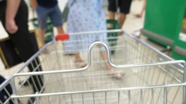 zaostřená v zaostření nákupního vozíku. rozmazané pozadí. Kupující výběr produktů v supermarketu.