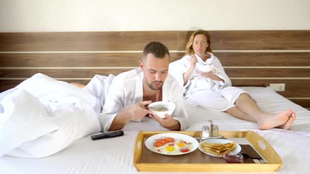 junges Paar, das morgens zusammen im Bett liegt, frühstückt im Bett