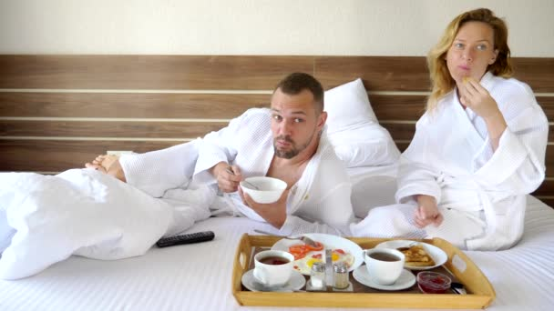 young couple lying in bed together in the morning, have breakfast in bed