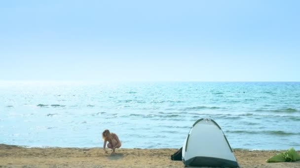 Camping concept by the sea. Girl collects shells on the beach near the tent on a background of the sea.
