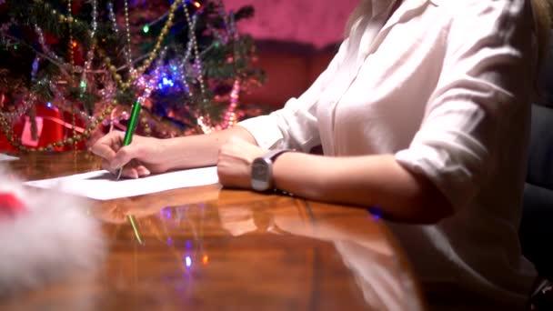 obchodní žena sedí u stolu u zdobených vánočních stromku a píše vánoční dopis pro Santa Klause