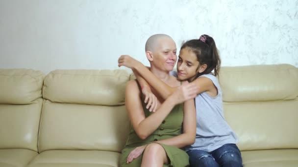 plešatý vyčerpaná matka po onkologii chemoterapie objetí její teenager dcera zatímco sedí na gauči