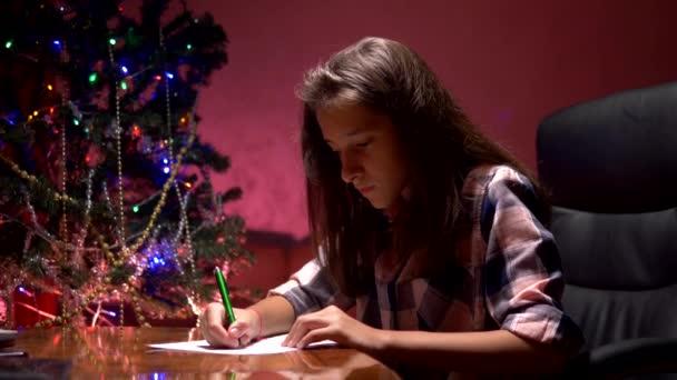 dívka sedí u stolu u zdobených vánočních stromku a píše vánoční dopis pro Santa Clause.