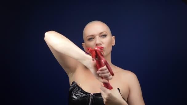 Velmi krásná plešatá žena v černém koženém korzetu s bičem a želízky na tmavém pozadí. kopírovat prostor