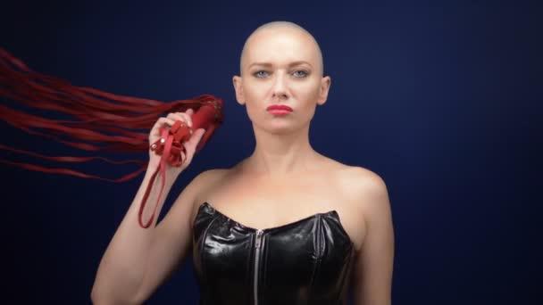 Sehr schöne Frau mit Glatze in einem schwarzen Lederkorsett mit Peitsche und Handschellen auf dunklem Hintergrund. Kopierraum