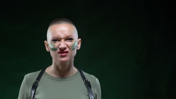 brutal bald woman with camouflage makeup holds a white massager in her hand