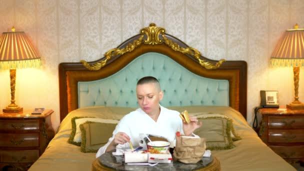 hladová holohlavá dívka v županu jí rychlé občerstvení sedí v luxusním interiéru na posteli