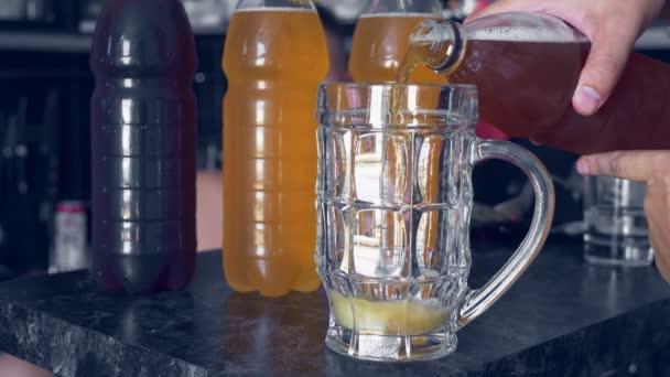 Bier wird gegen Plastikflaschen mit verschiedenen Biersorten in einen Becher geschüttet